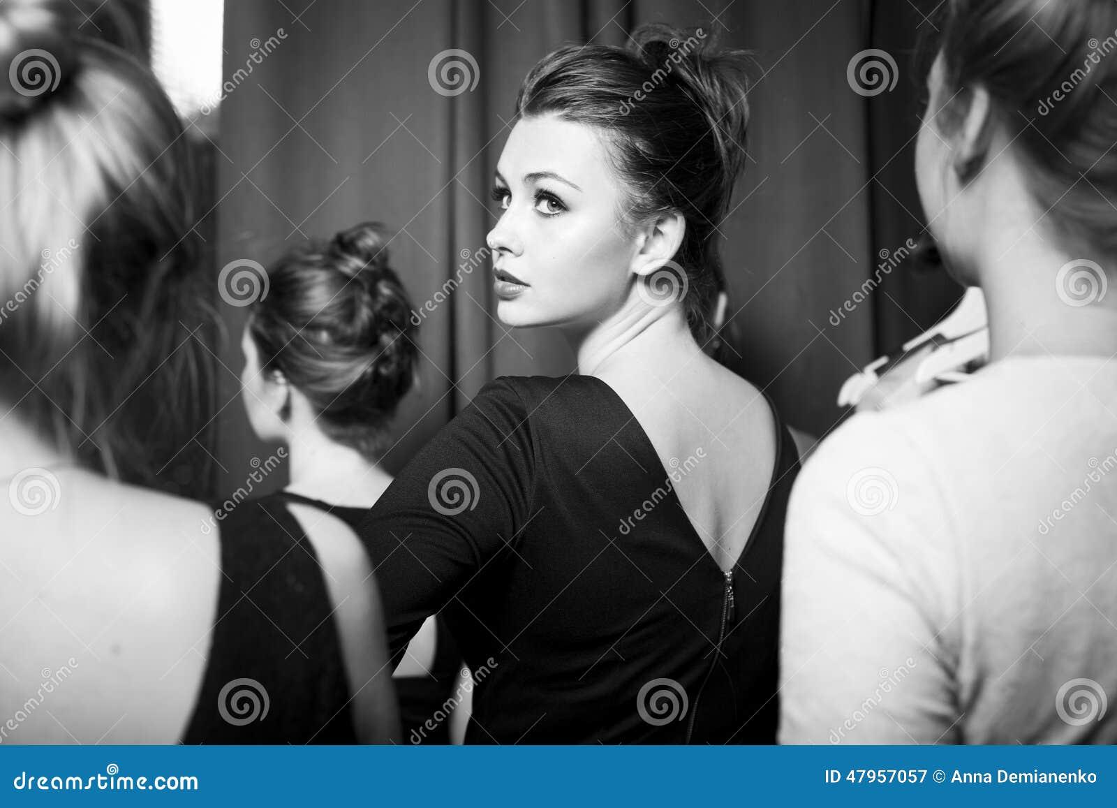 Mode-Modelle vorbereitet für Rollbahn vom stilvollen Designer Mädchen versteckt sich im Hemd eines Mannes
