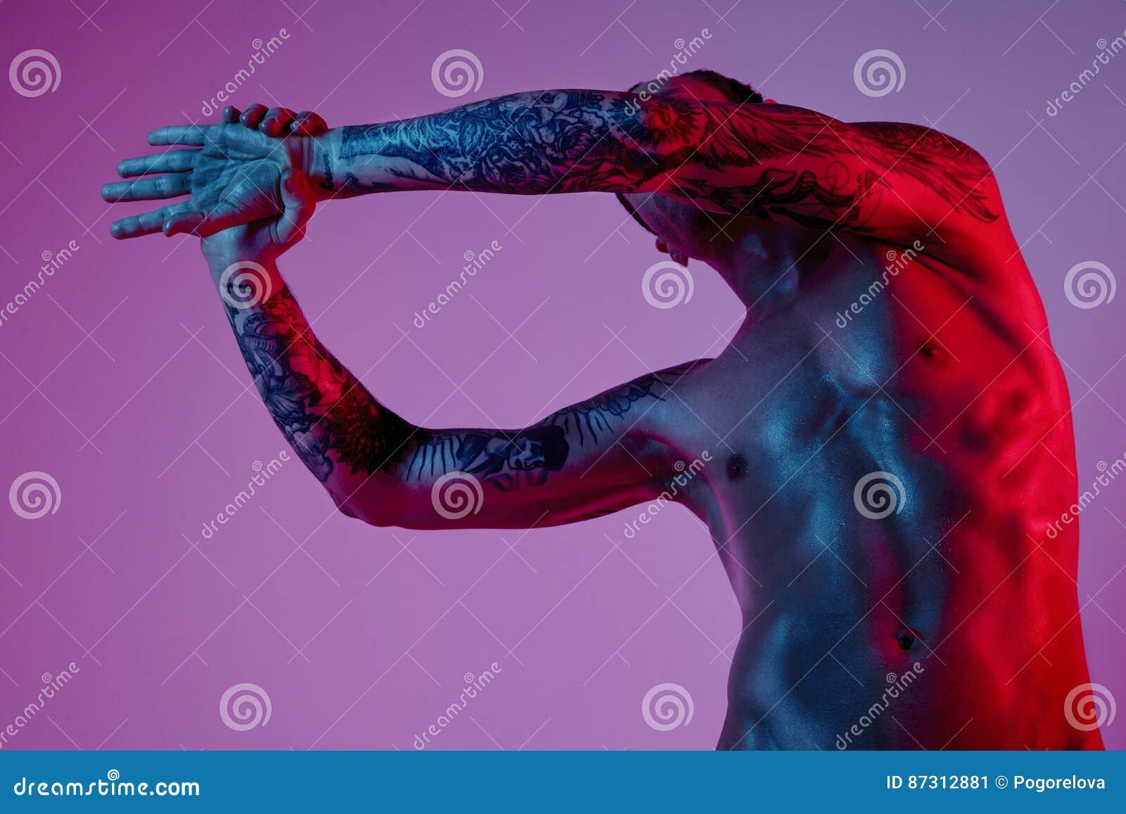 Mode photoshoot des attraktiven Mannes des Sportsitzes, der Arm herstellt auszudehnen Männlicher nackter Körper, tätowierte Hände