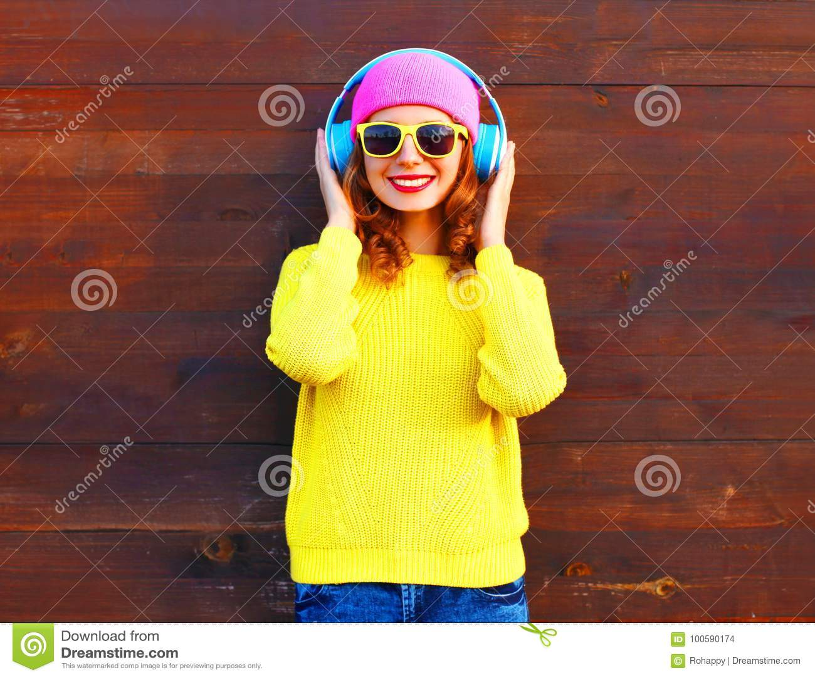 Mode som ler flickan, lyssnar till musik i hörlurar, färgrik pi