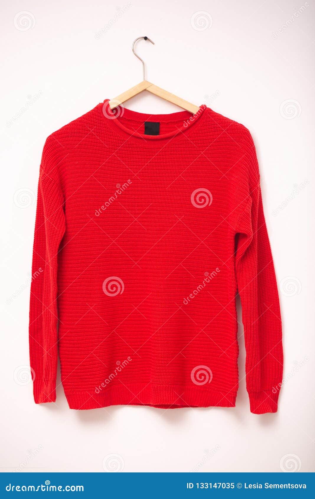 Mode und Kleidungskonzept Rote gestrickte warme Strickjacke der Frau auf Aufhängern gegen weißen Hintergrund Vertikaler Schuss