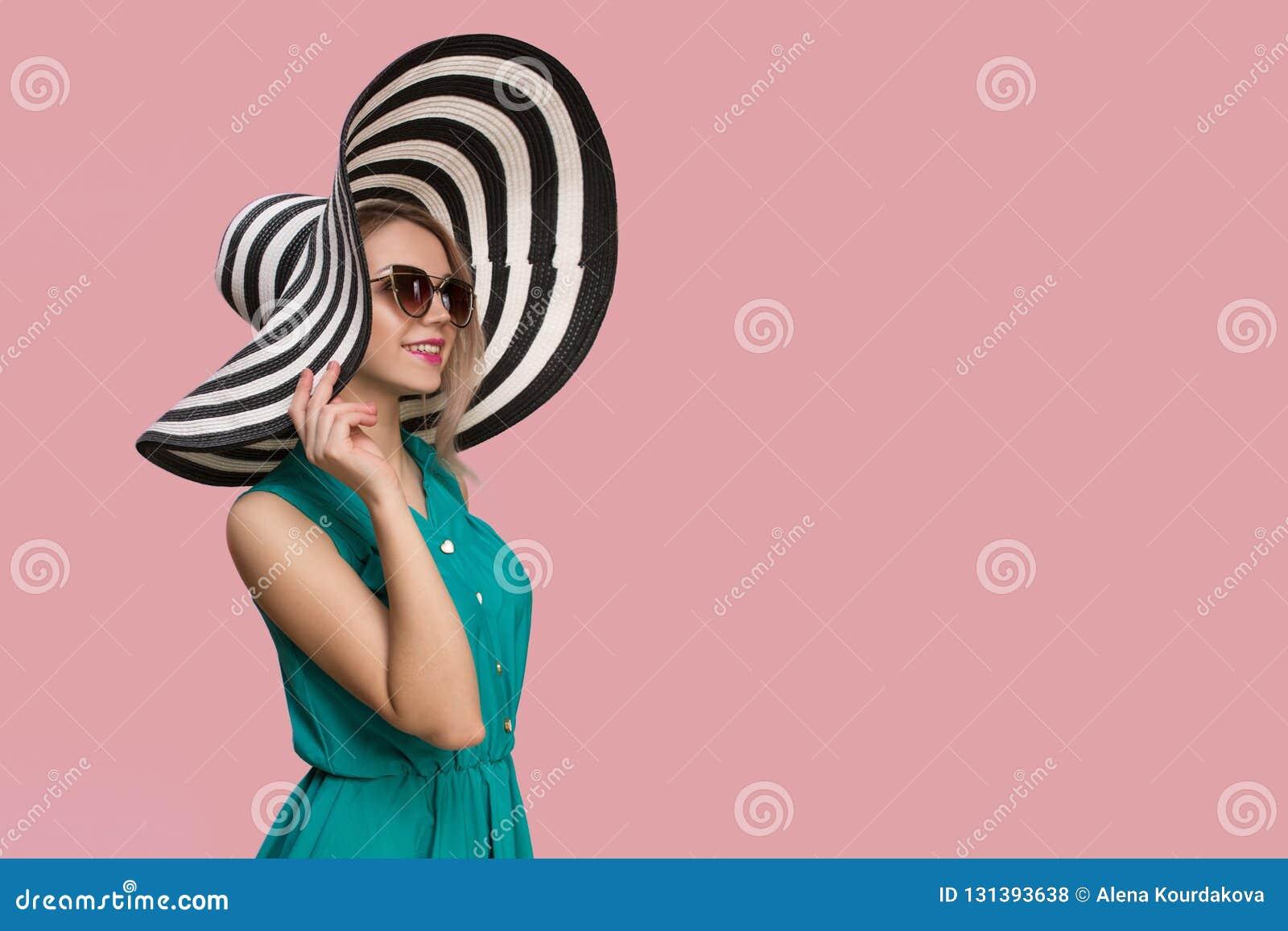 Modeflicka i en stor hatt och solglasögon på en kulör bakgrund