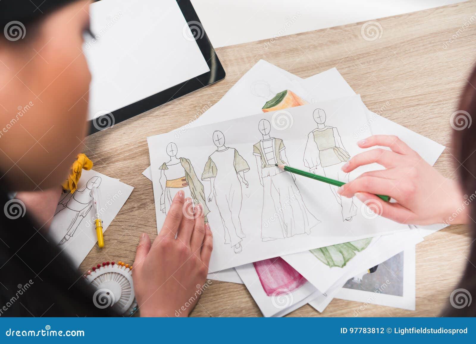 Modeformgivare som arbetar med ritningar av modeller på tabellen