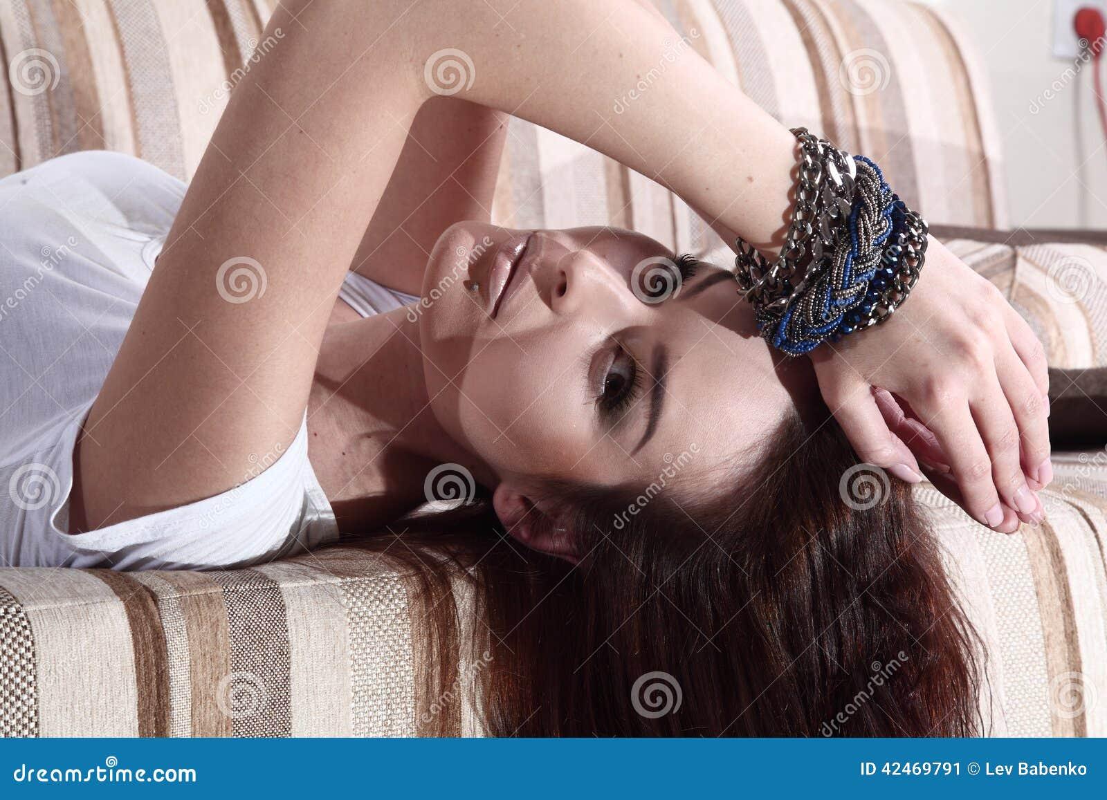 Modefrau liegt, schönes braunes Haar unten im weißen Hemd