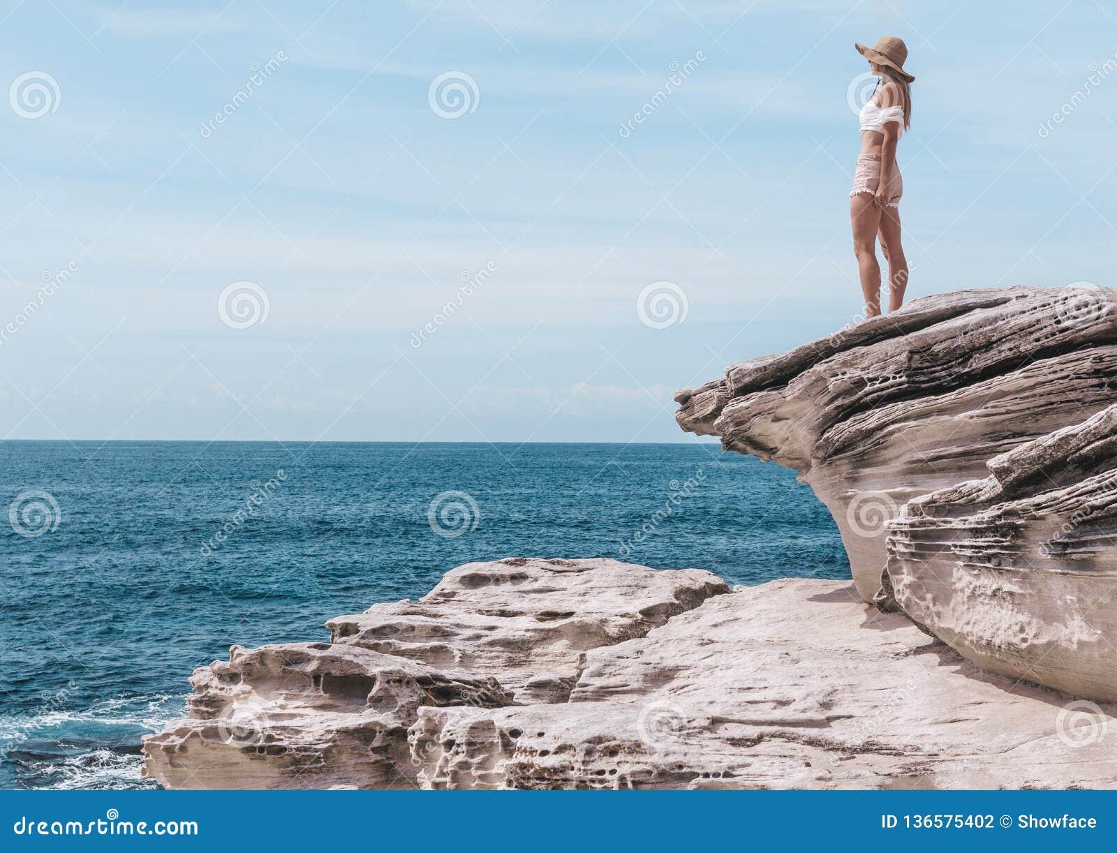 Modefrau, welche die Sommersonne durch die Küste genießt