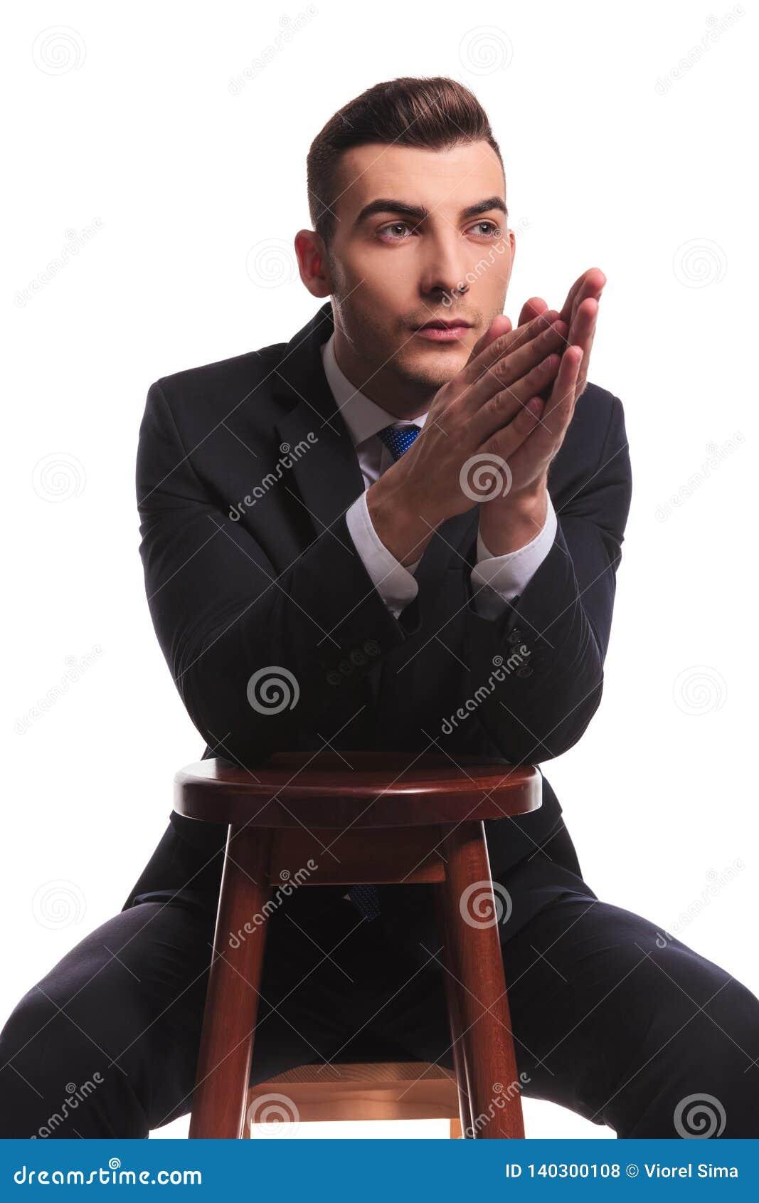 Modekerl in der Klage, die mit den betenden Händen zufriedengestellt schaut