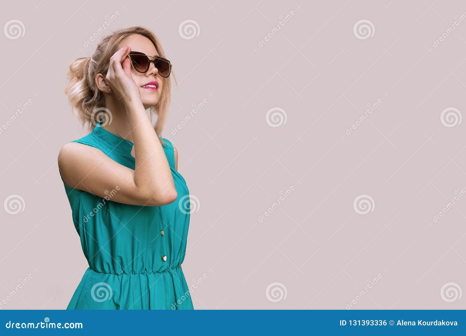Modekvinna i solglasögon på en grå bakgrund