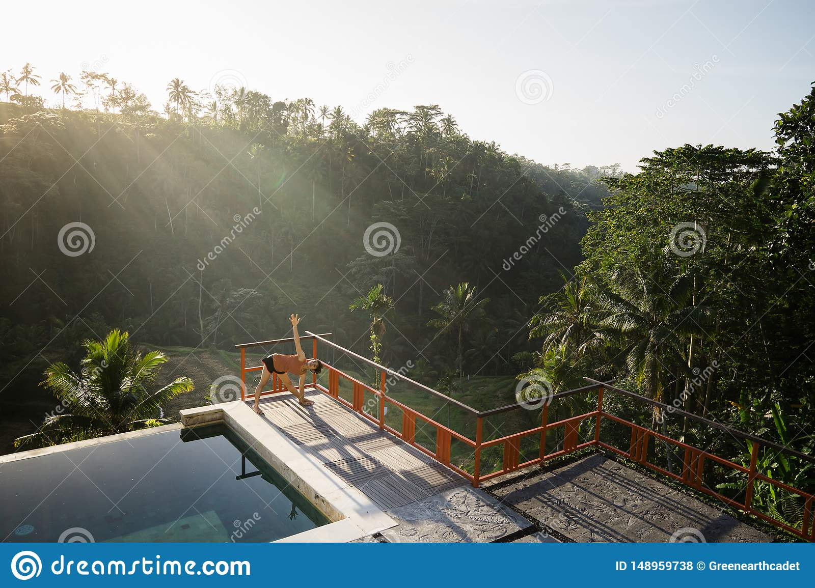 A model of a beautiful, short-haired and young woman doing yoga with Natarajasana poses by the pool with views of rice fields and