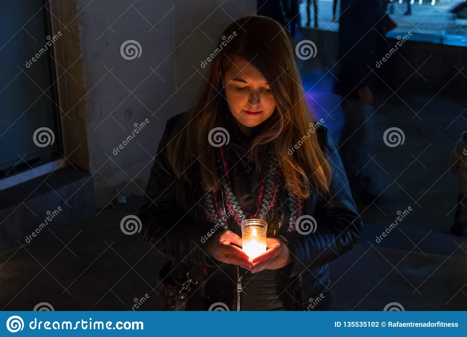 Model with black jacket in night photo with candles