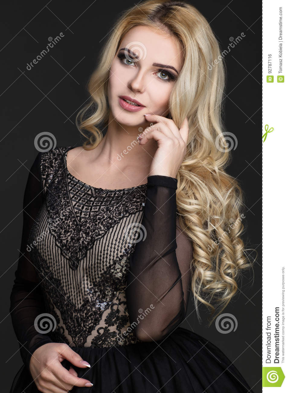Model with blonde hair wearing dress with pattern.