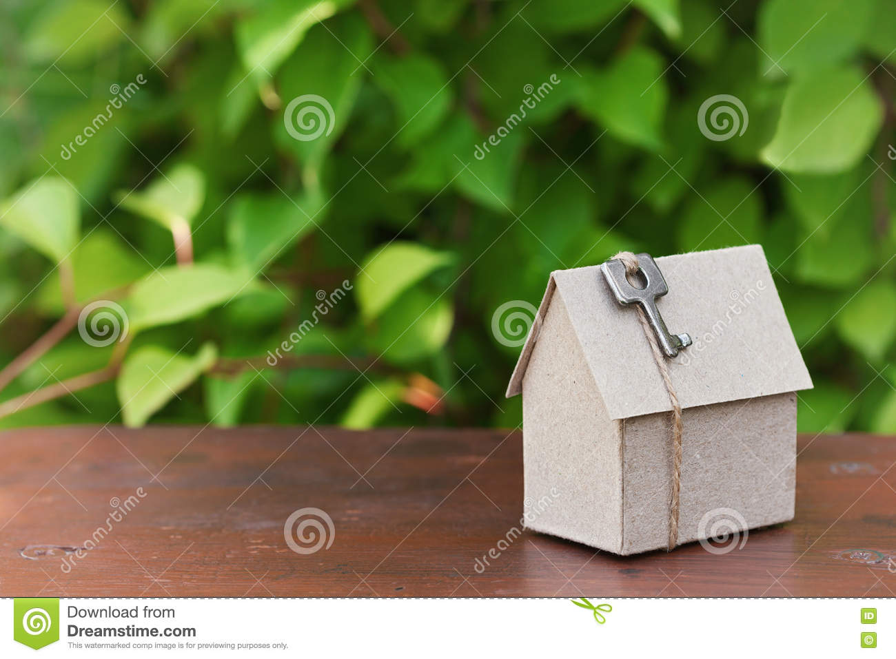 Model of cardboard house with key against green leaves background. Purchase, rent and construction country real estate concept.