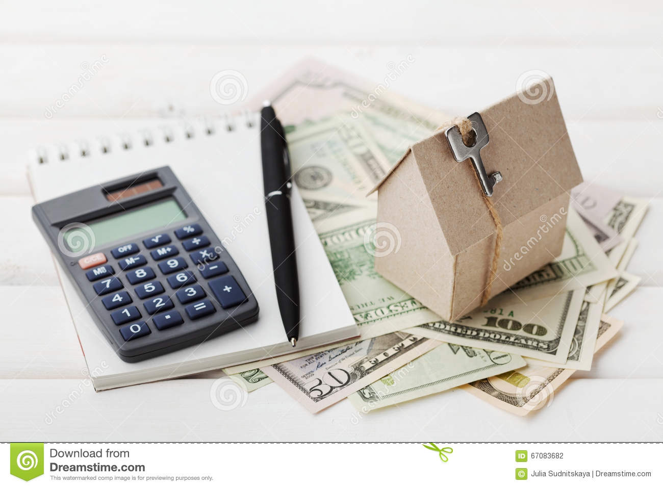 Model of cardboard house with key calculator notebook for Home construction calculator