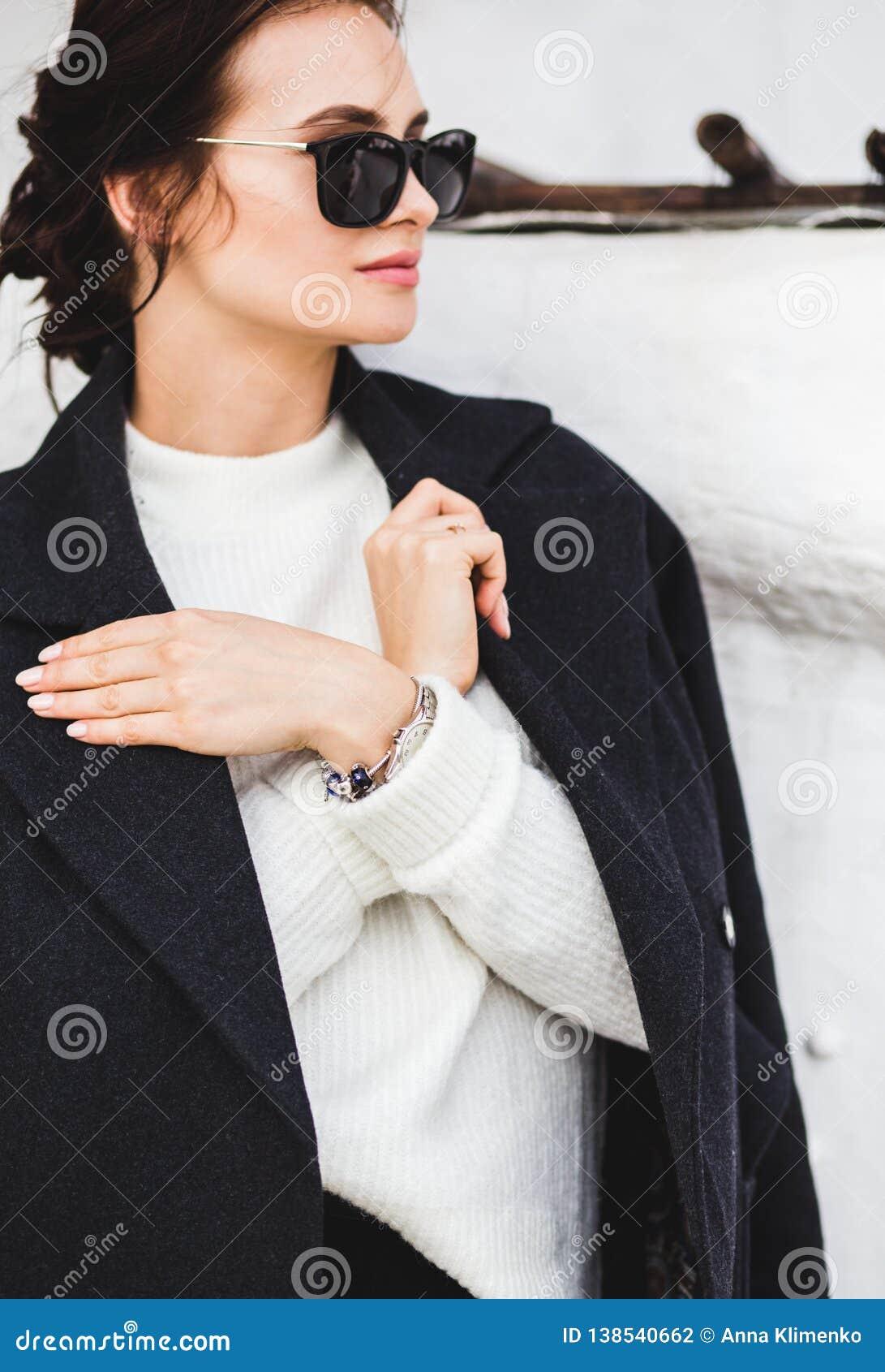 Model die van de manier het mooie vrouw een donkere laag en een witte sweater, in zonnebril dragen, die over witte achtergrond st