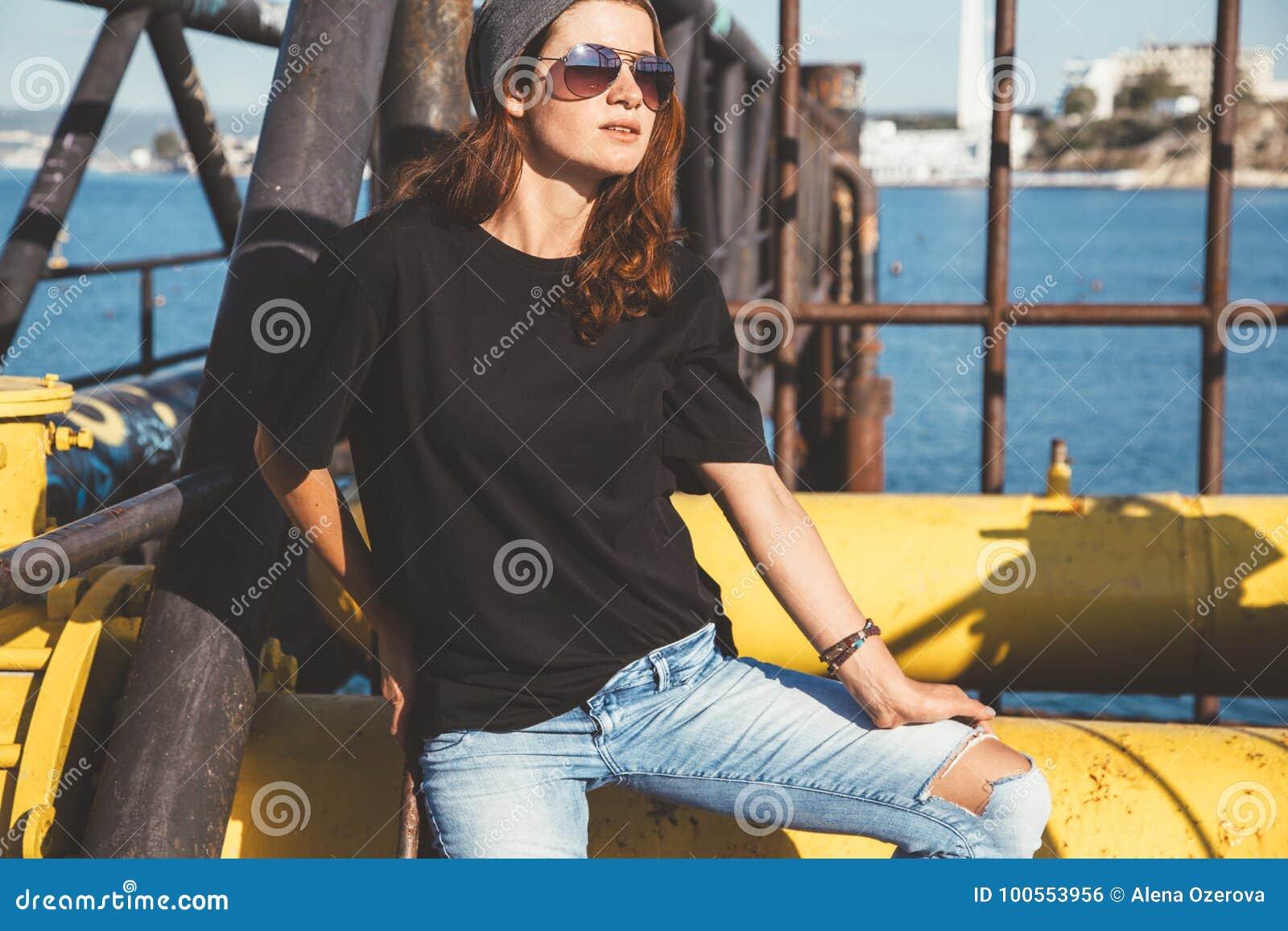 Model dragende duidelijke t-shirt en zonnebril die over straat stellen wal