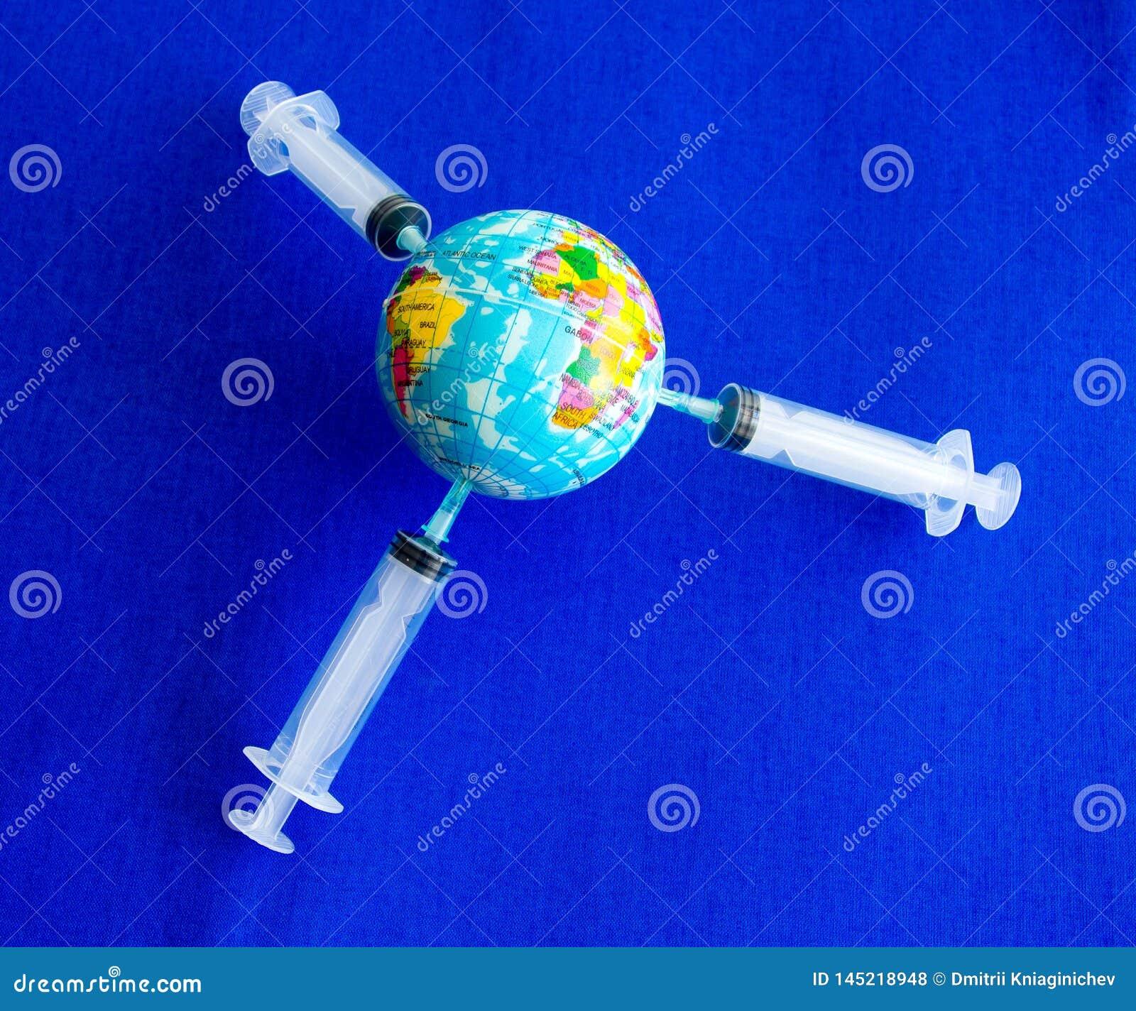 The model earth on the syringe on blue background- image