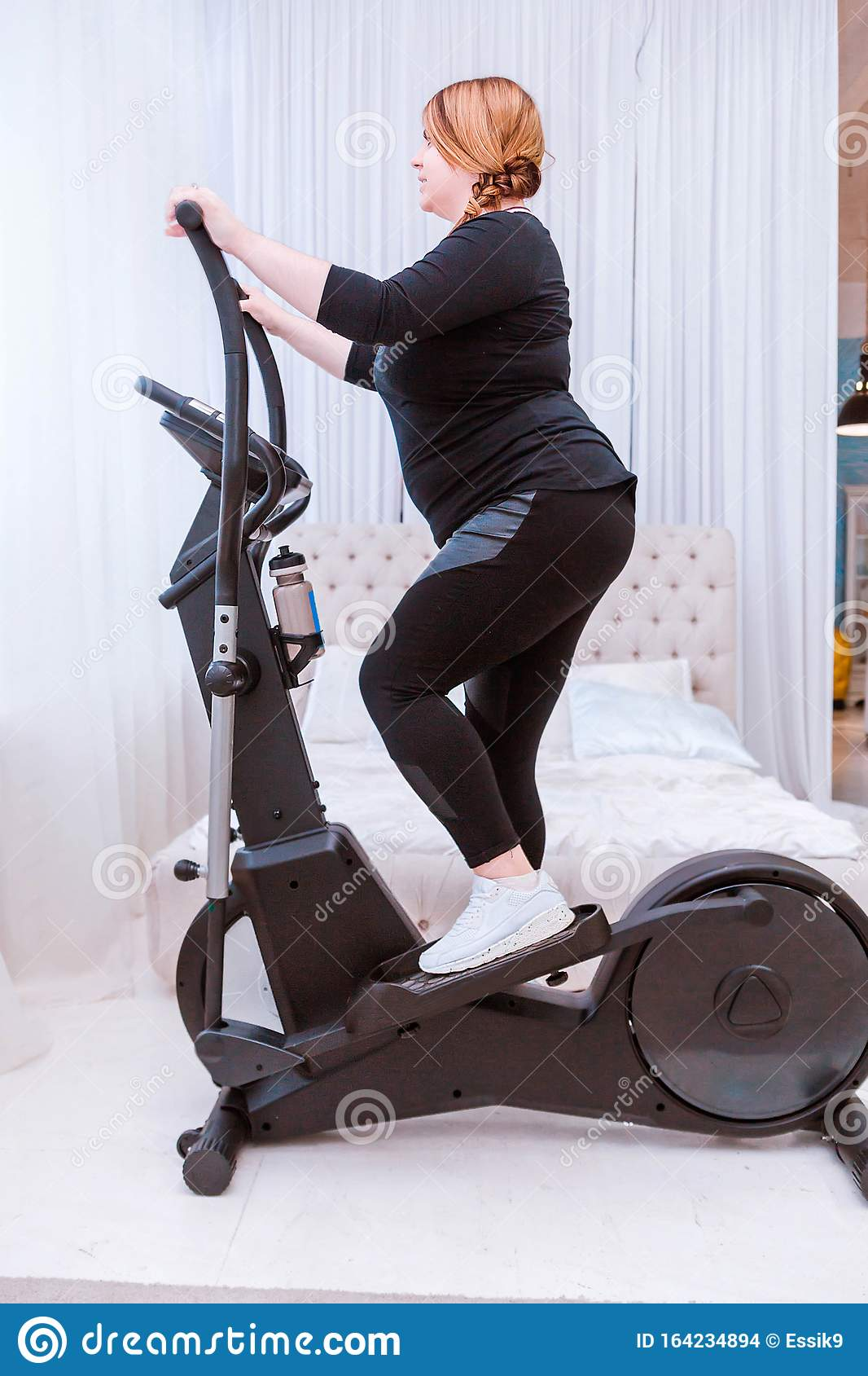 Model - A Fat Woman, Trying To Lose Weight And At Home Is Engaged In An  Elliptical Trainer Stock Photo - Image of fitness, machine: 164234894