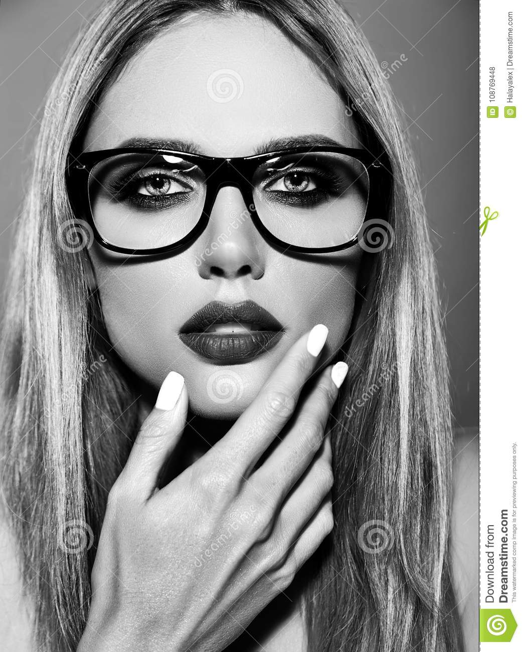 Model with fresh daily makeup with dark lips color and clean healthy skin on red background in glasses