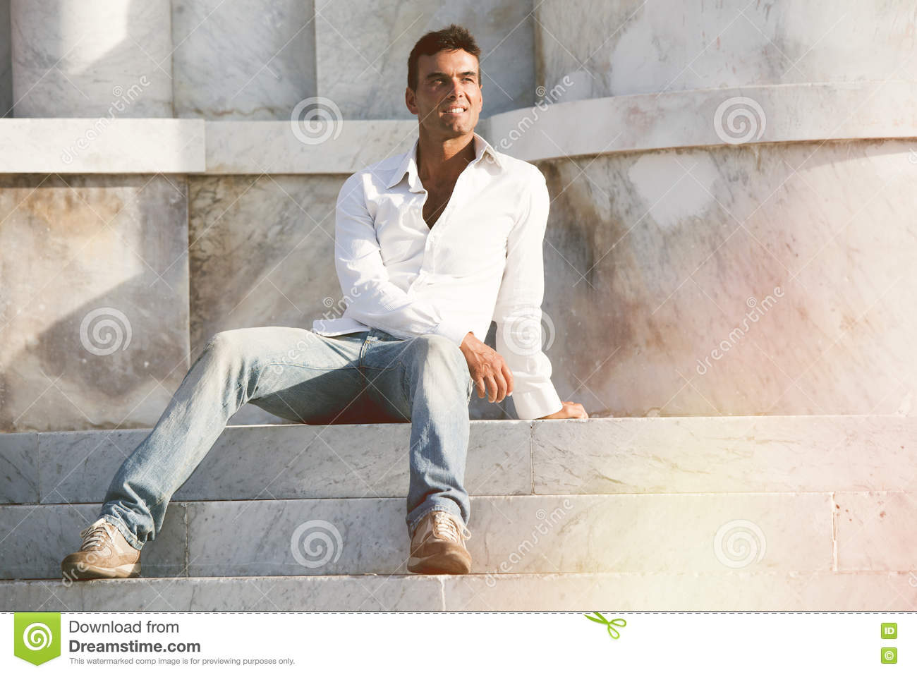 Model Handsome Man Relaxed Sitting On The Steps Of White