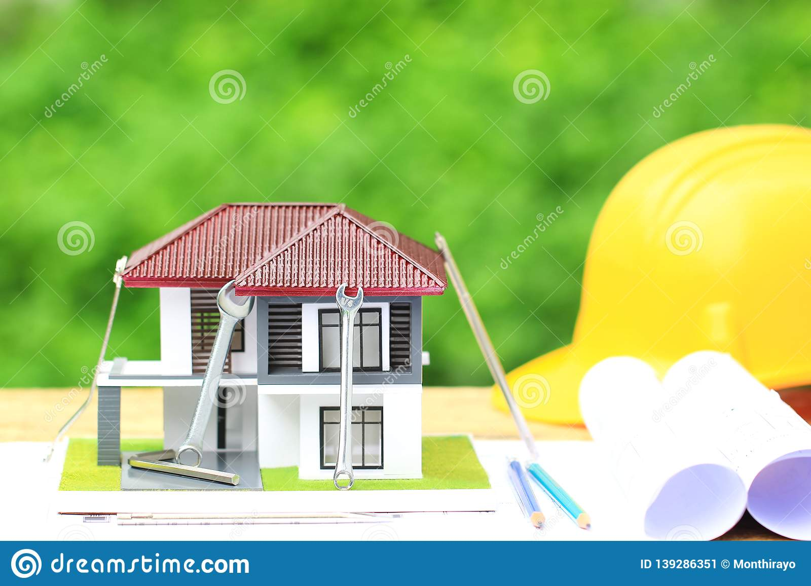 Model house and construction tools with Yellow helmets and architect rolls plans on natural green background, Repair maintenance