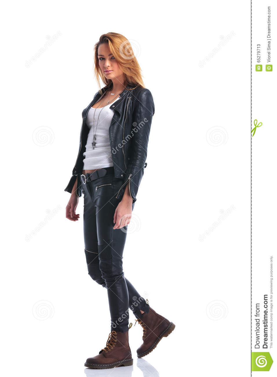 Model pose in leather jacket while walking in studio and looking