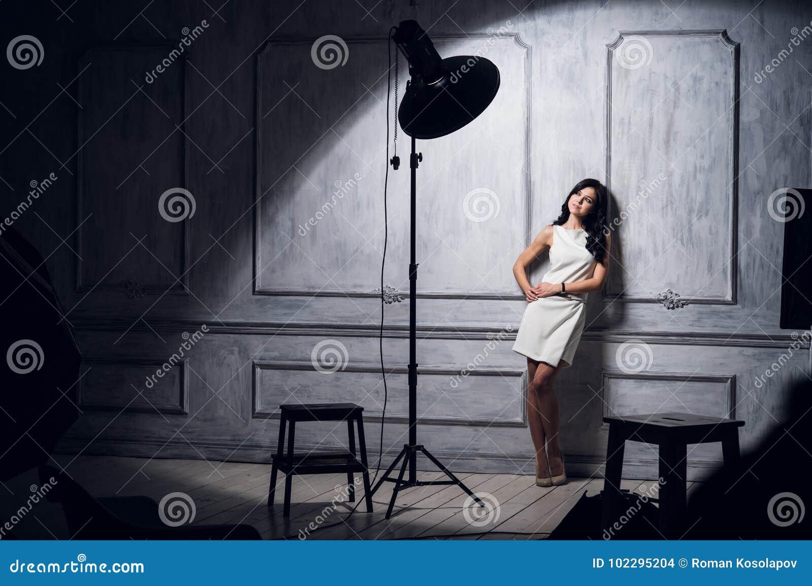 Model posera för härlig kvinnlig på studion i de ljusa exponeringarna