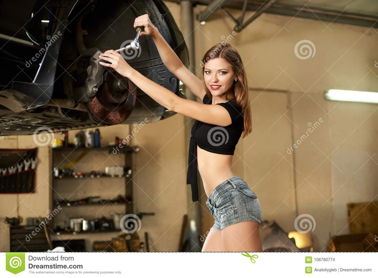 Model poses with socket wrench near car on hydraulic lift