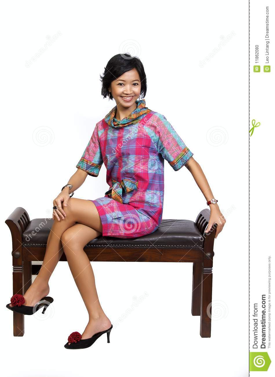 Beautiful asian model sitting on chair in the studio, looking fresh.