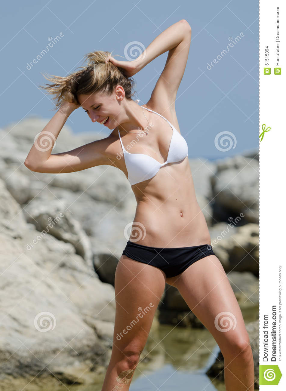 Tall slim female model standing between sea rocks wearing a black and white  bikini. Hands on head looking down and laughing.Vertical photo