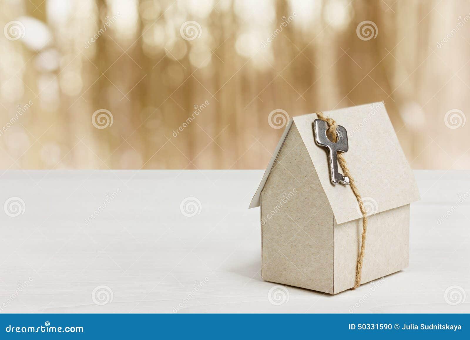 Model van kartonhuis met sleutel tegen bokehachtergrond woningbouw, onroerende goederen lening, of kopend een nieuw huis
