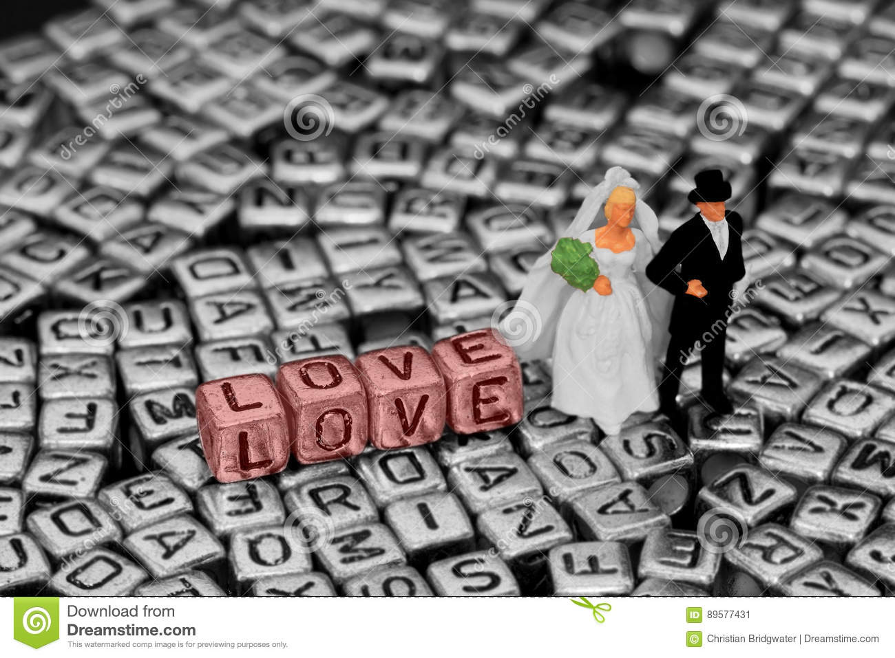 model wedding couple standing on letter jewellery beads