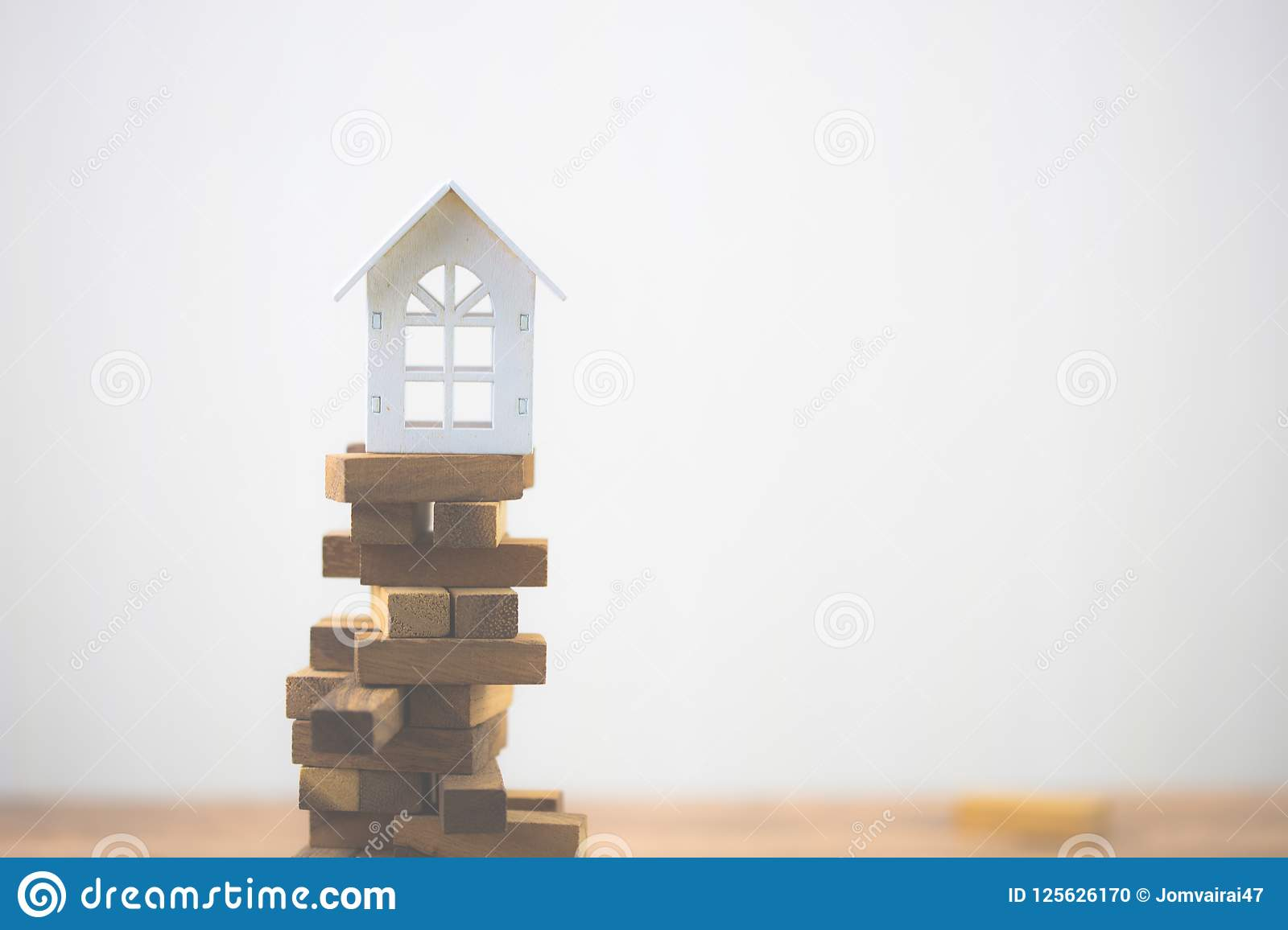 Model white house on wood block. Investment risk and uncertainty in the real estate housing market.