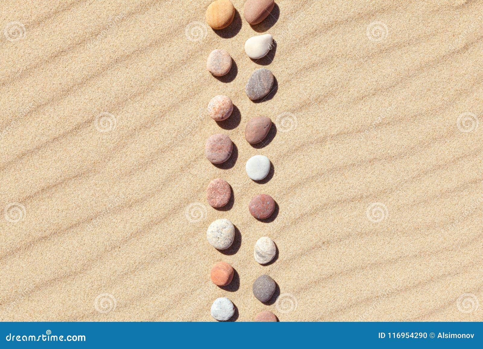 Modell av kulöra kiselstenar på ren sand Zenbakgrund, harmoni och meditationbegrepp