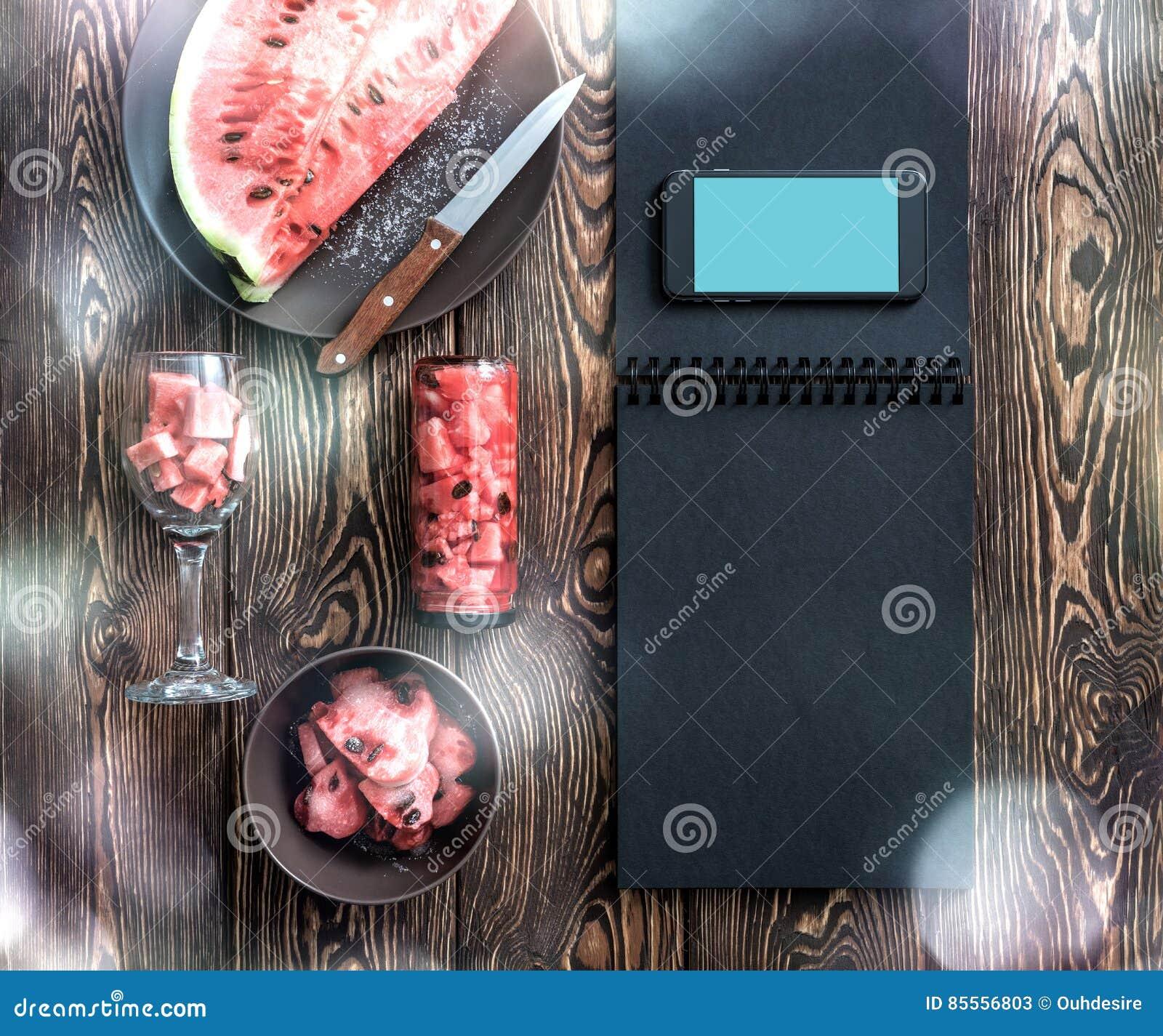 Modell des Smartphone nahe bei Wassermelonenscheiben Über Weiß