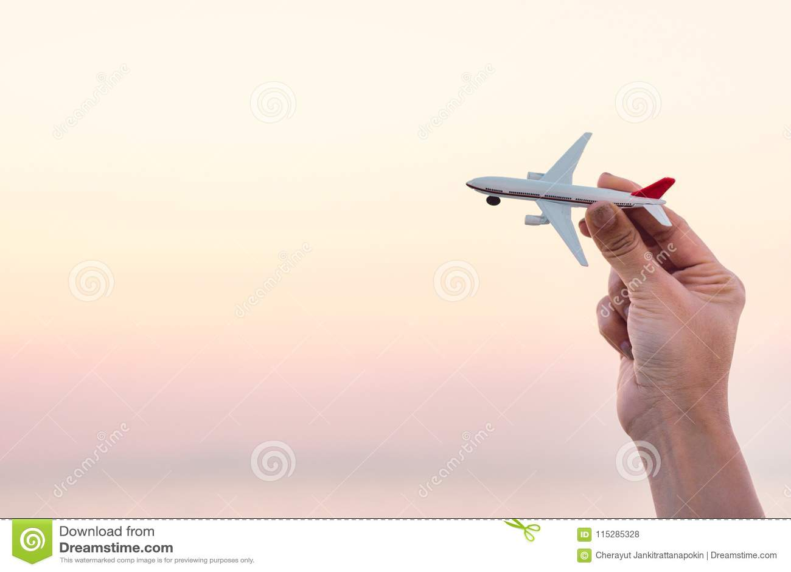 Modell för flygplan för kvinnahand hållande i solnedgånghimmel och sommarhav b