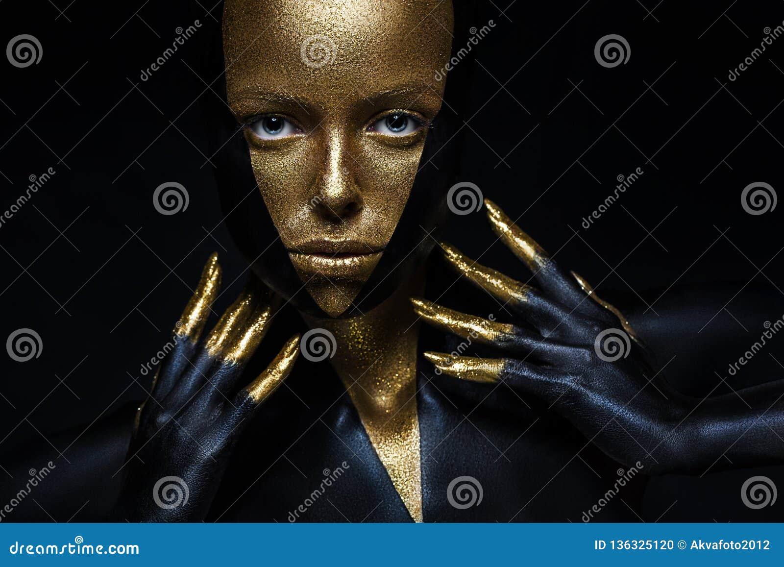Modell för högt mode med svart och guld- läder, guld- fingrar Isolerat på kvinnlig framsida för svart bakgrundsskönhet,
