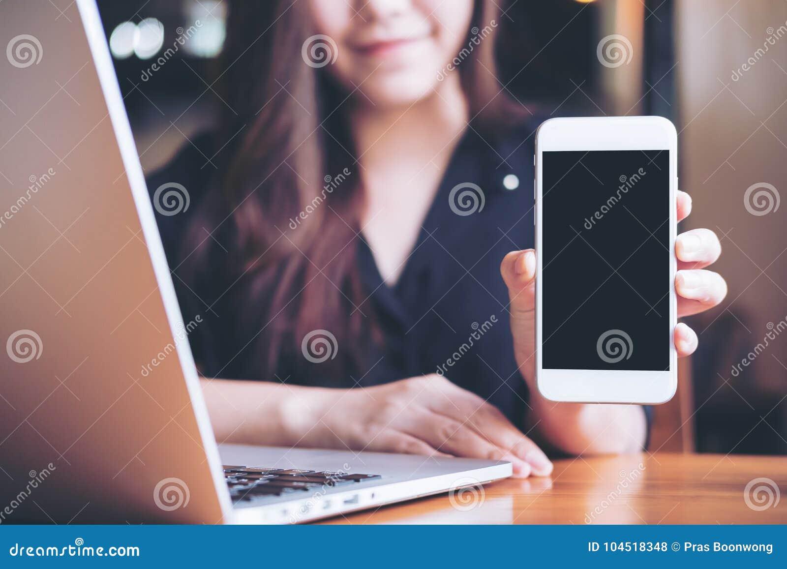 Modellbild einer asiatischen Schönheit des smiley, die weißen Handy mit leerem schwarzem Schirm bei der Anwendung des Laptops häl