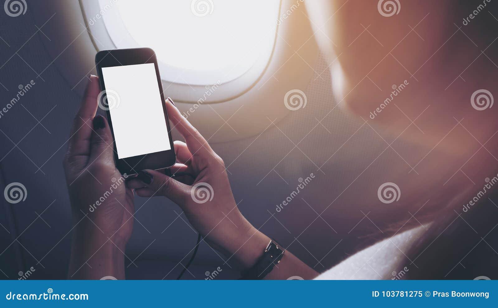 Modellbild einer Frau, die schwarzes intelligentes Telefon mit schwarzem weißem Schirm nahe bei einem Flugzeugfenster hält und be