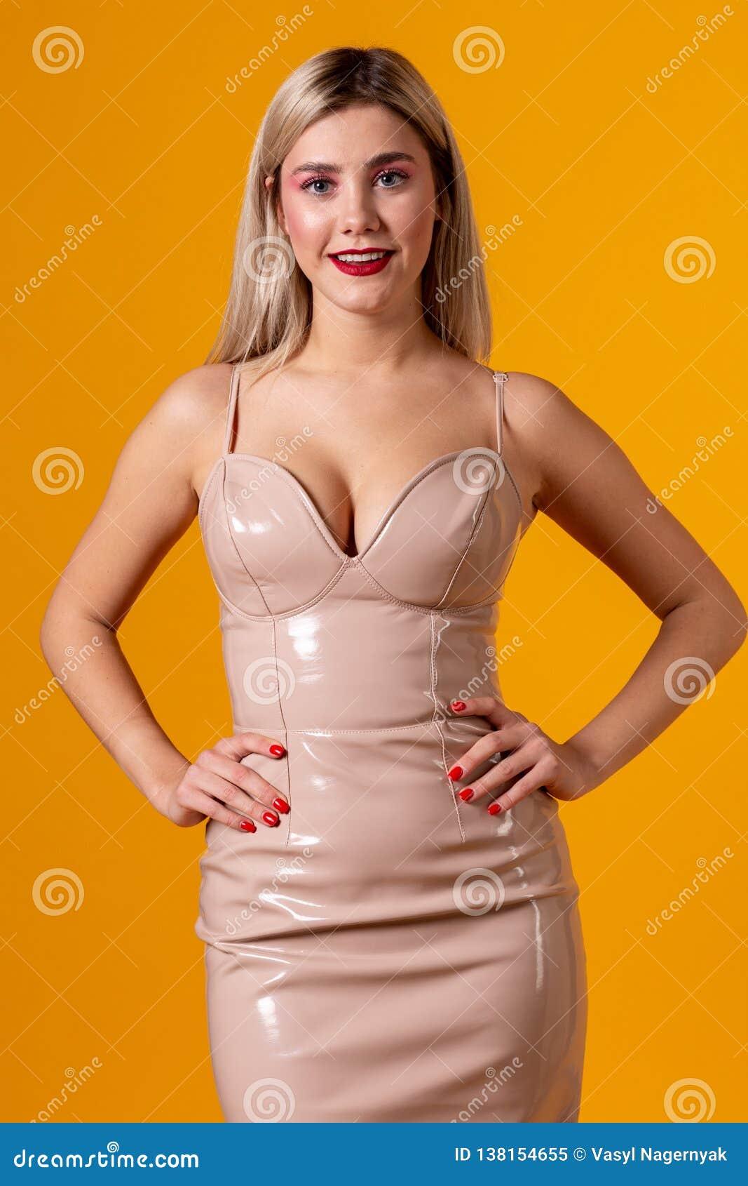 Modello biondo splendido che dura in vestito di cuoio elegante dal creame con decollete