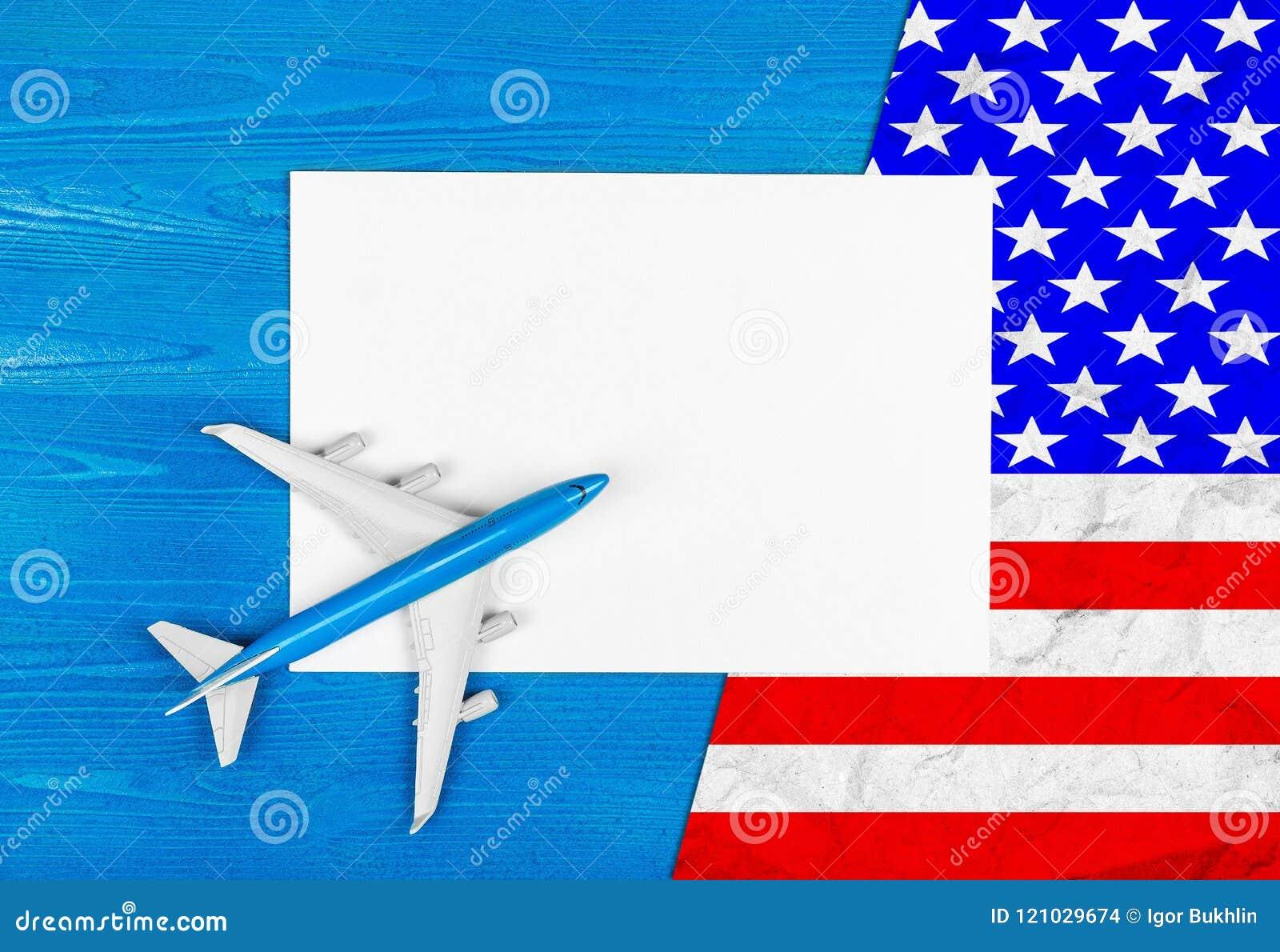 Modello dell aeroplano, del foglio bianco di carta e della bandiera di U.S.A. sui precedenti di legno blu concetto di corsa