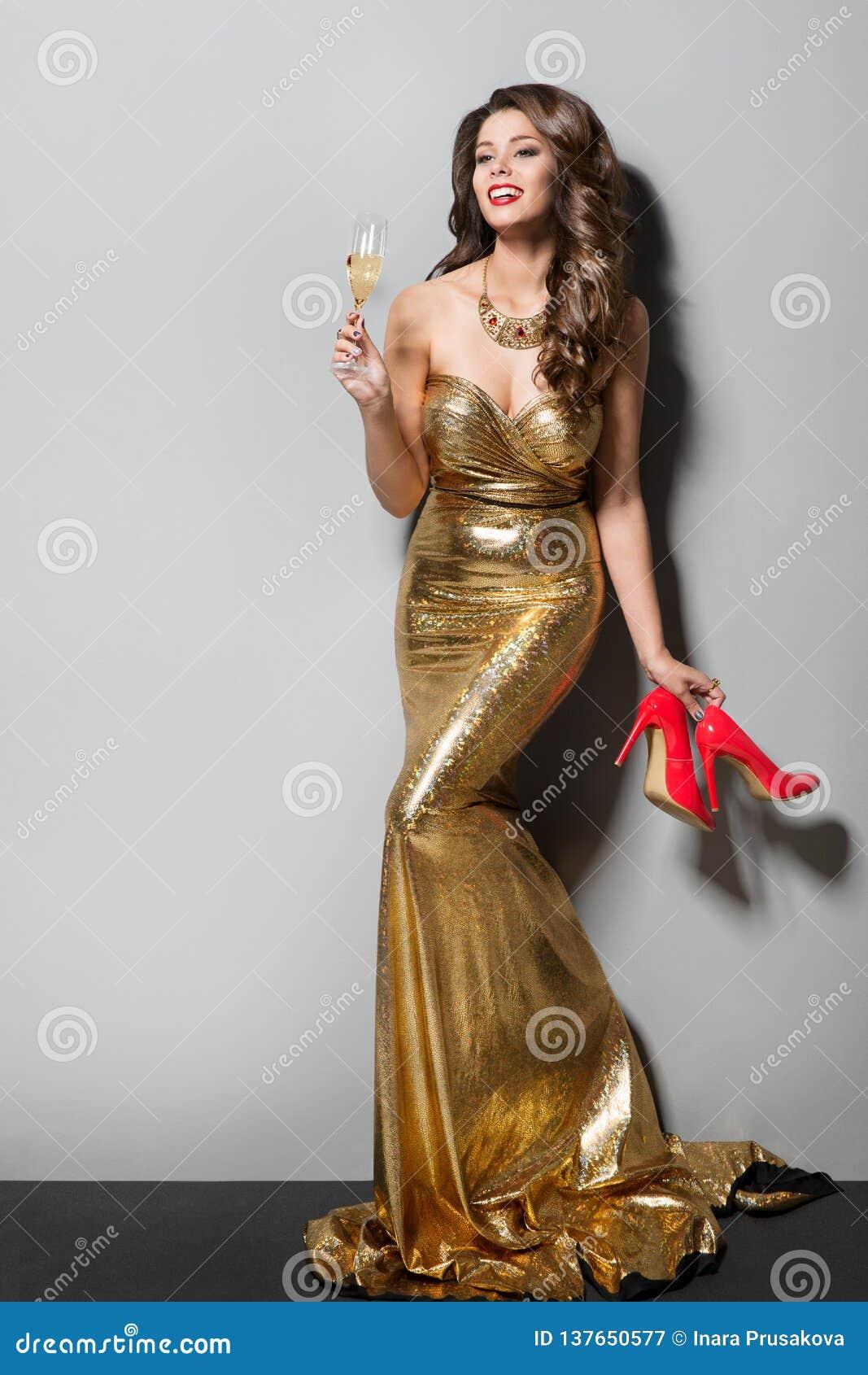 Modello di moda in vestito lungo dall oro che balla e che beve, donna elegante felice, scarpe del tacco alto