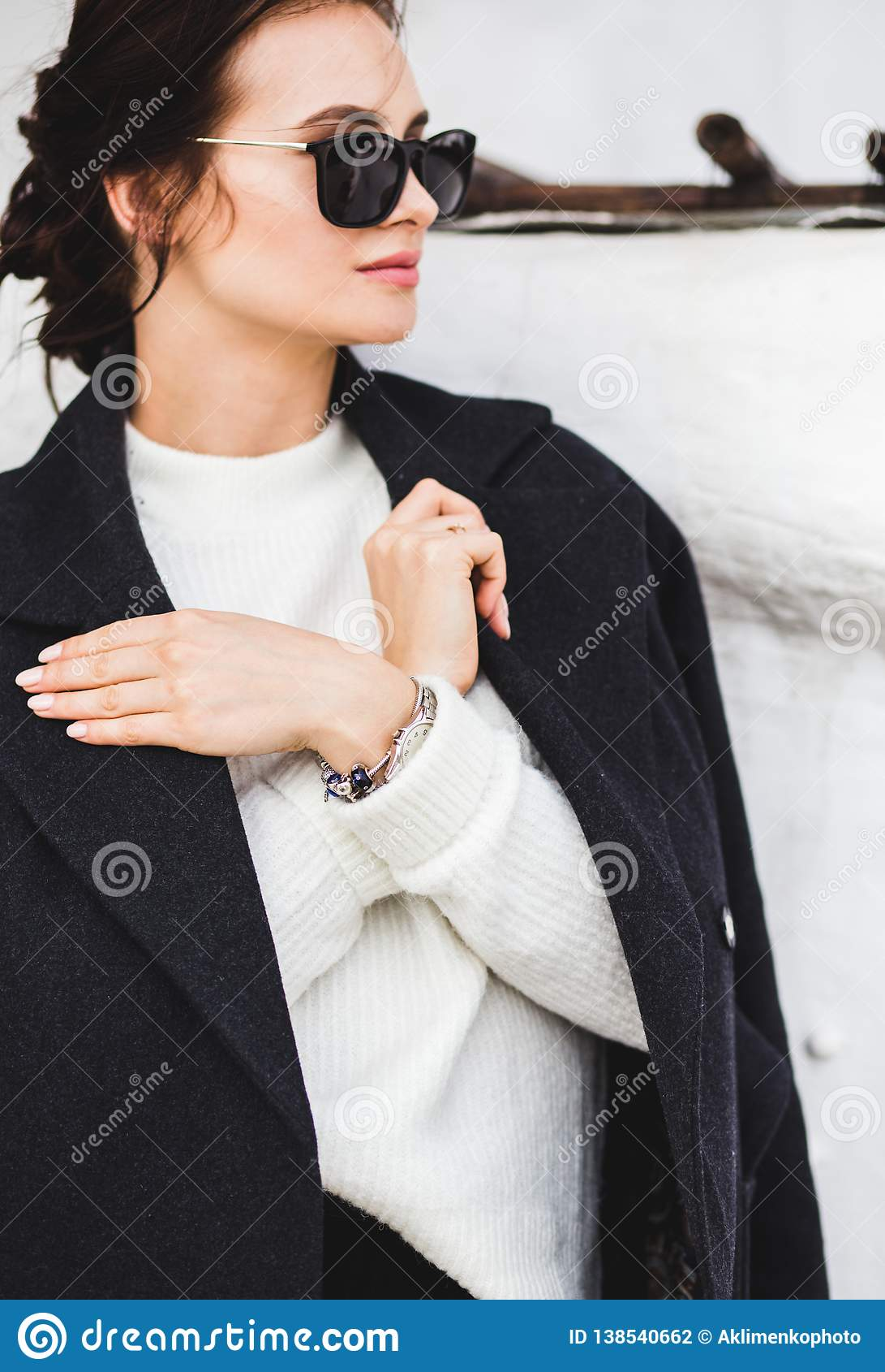 Modello grazioso della donna di modo che porta un cappotto scuro e un maglione bianco, in occhiali da sole, posanti sopra il fond