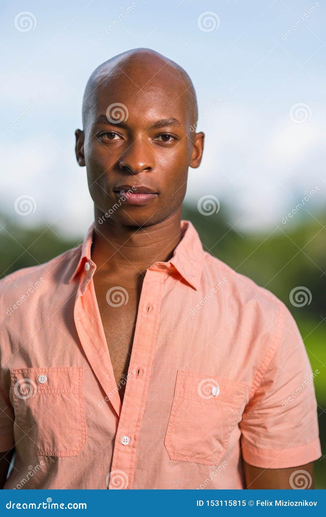 Modello maschio afroamericano bello del ritratto giovane che esamina macchina fotografica Uomo calvo che porta una camicia rosa d