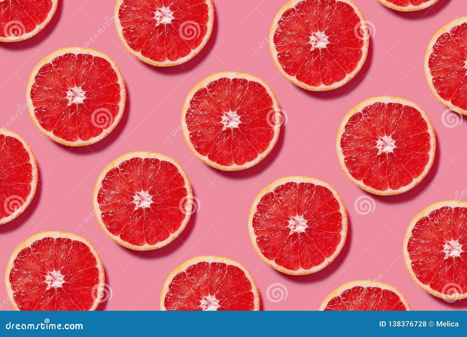 Modello variopinto della frutta delle fette fresche del pompelmo su fondo rosa