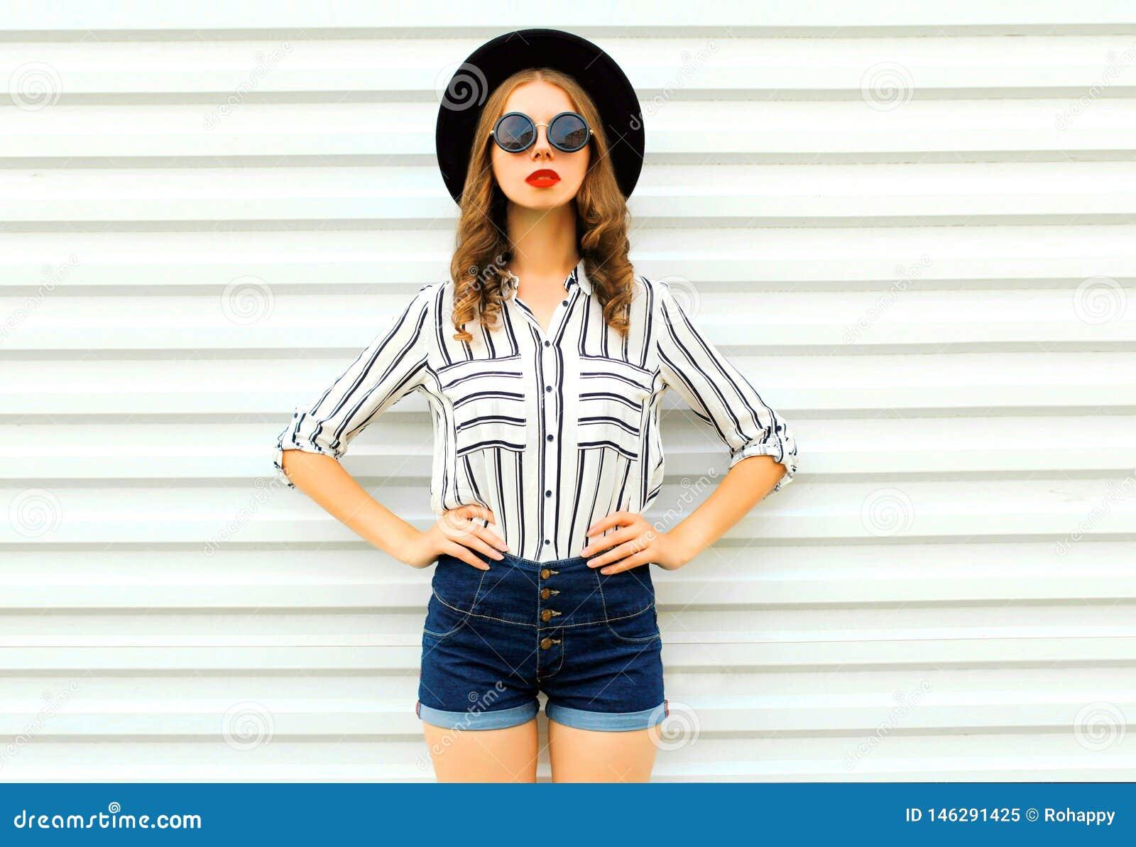 Modelo à moda da jovem mulher no chapéu redondo preto, short, camisa listrada branca que levanta na parede branca