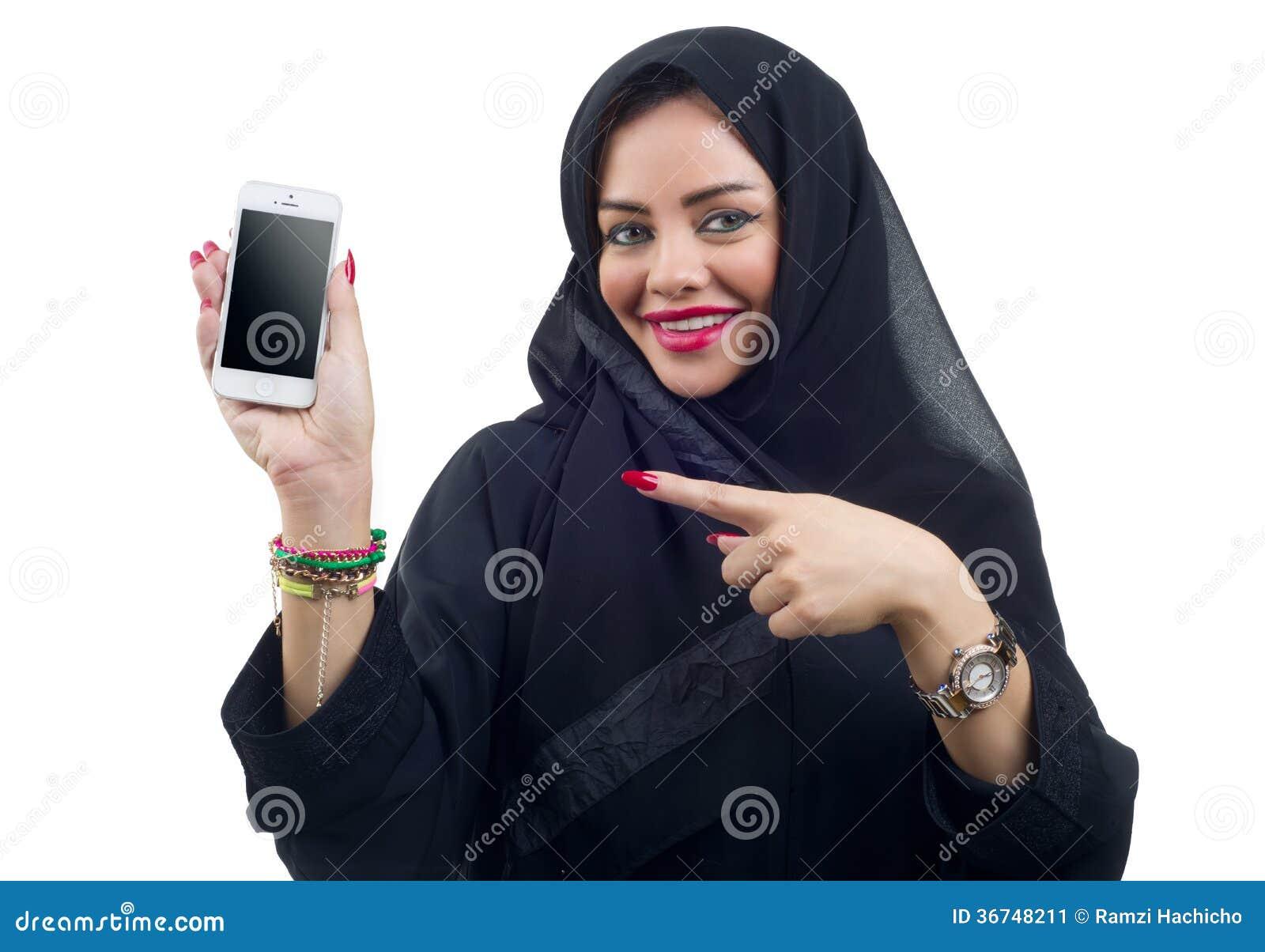 Modelo árabe bonito que guarda um telefone celular em um fundo isolado