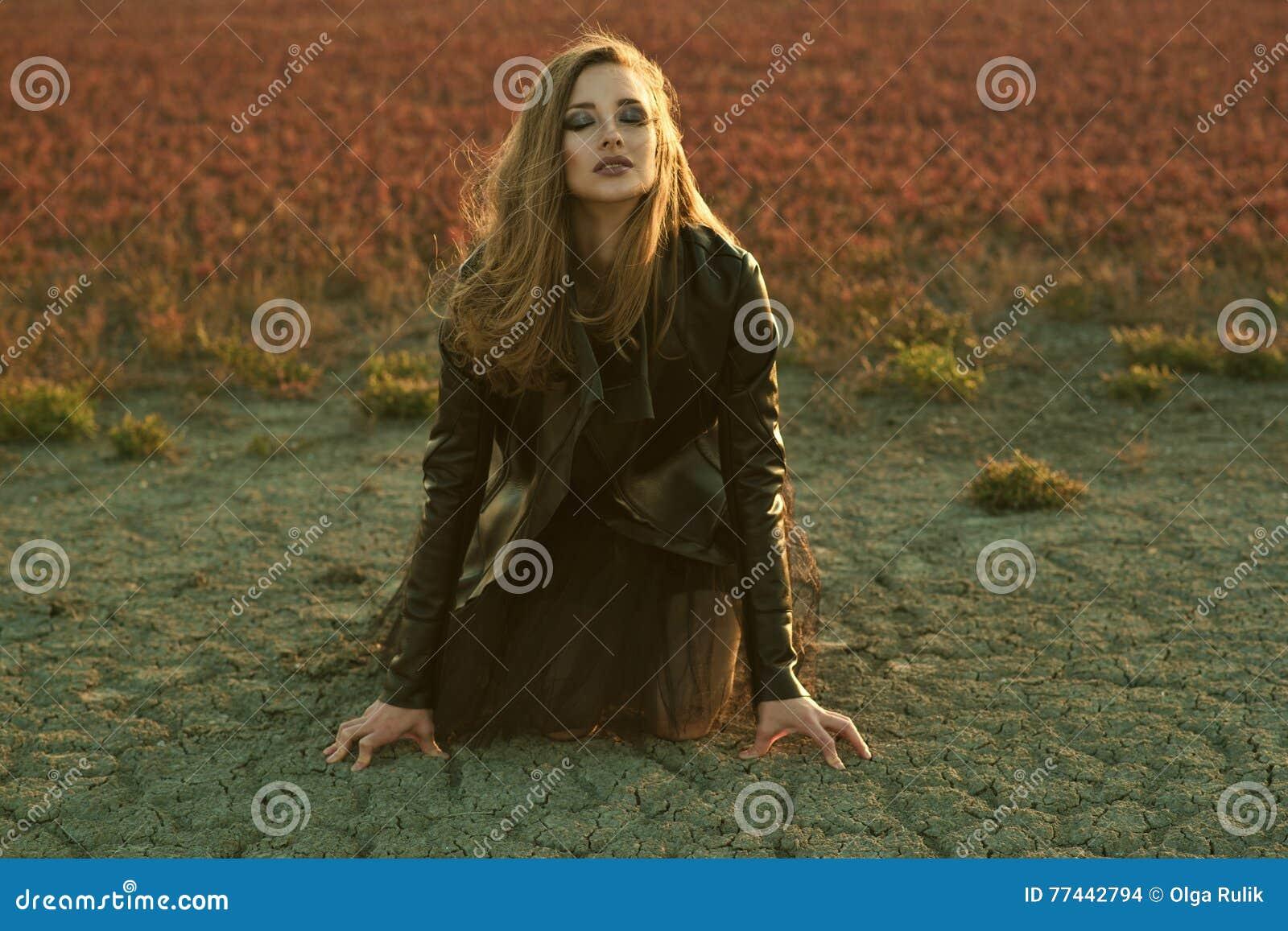 Modelo atractivo joven con el pelo largo en vestido que vela negro y la chaqueta de cuero elegante que se sientan en la tierra co