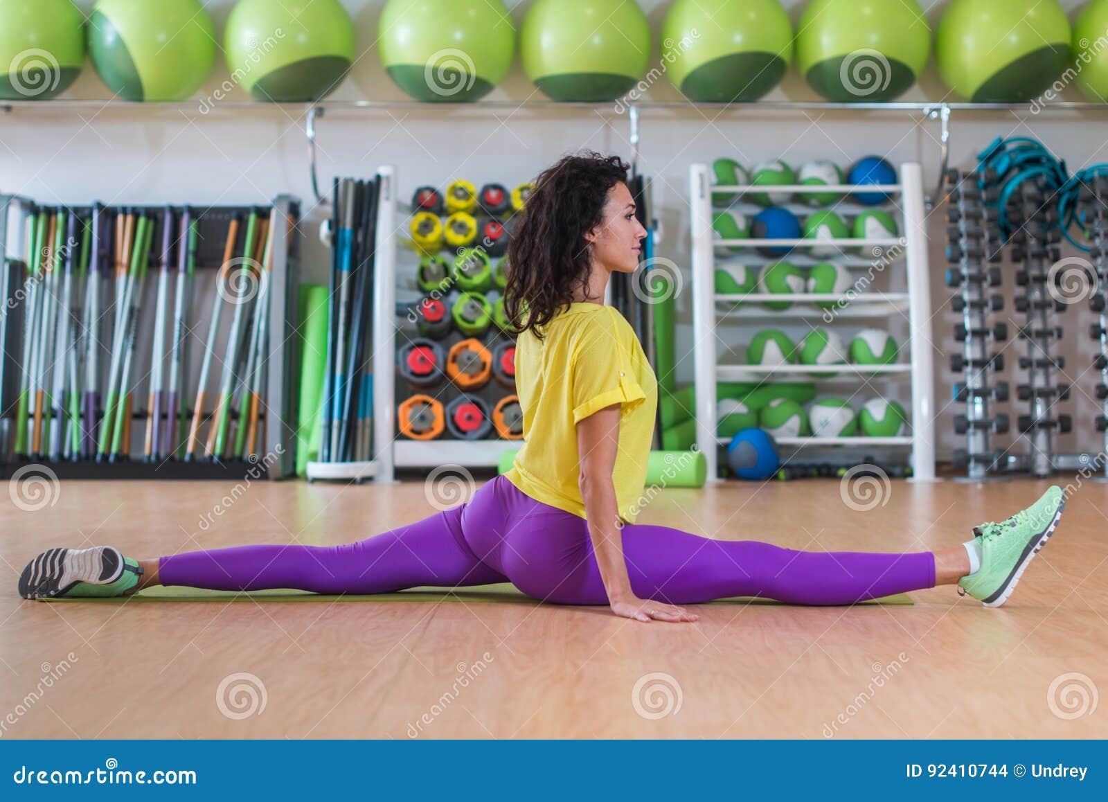 Modelo bonito da aptidão no sportswear que faz a separação da parte dianteira no gym, esticando seus pés, olhando a câmera e o so