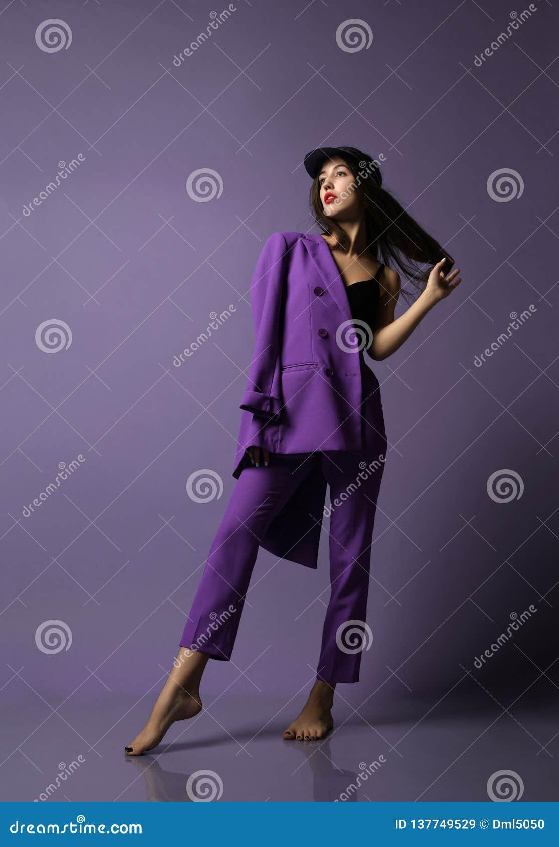 Modelo bonito da menina do moderno que levanta no terno e no roupa interior roxos