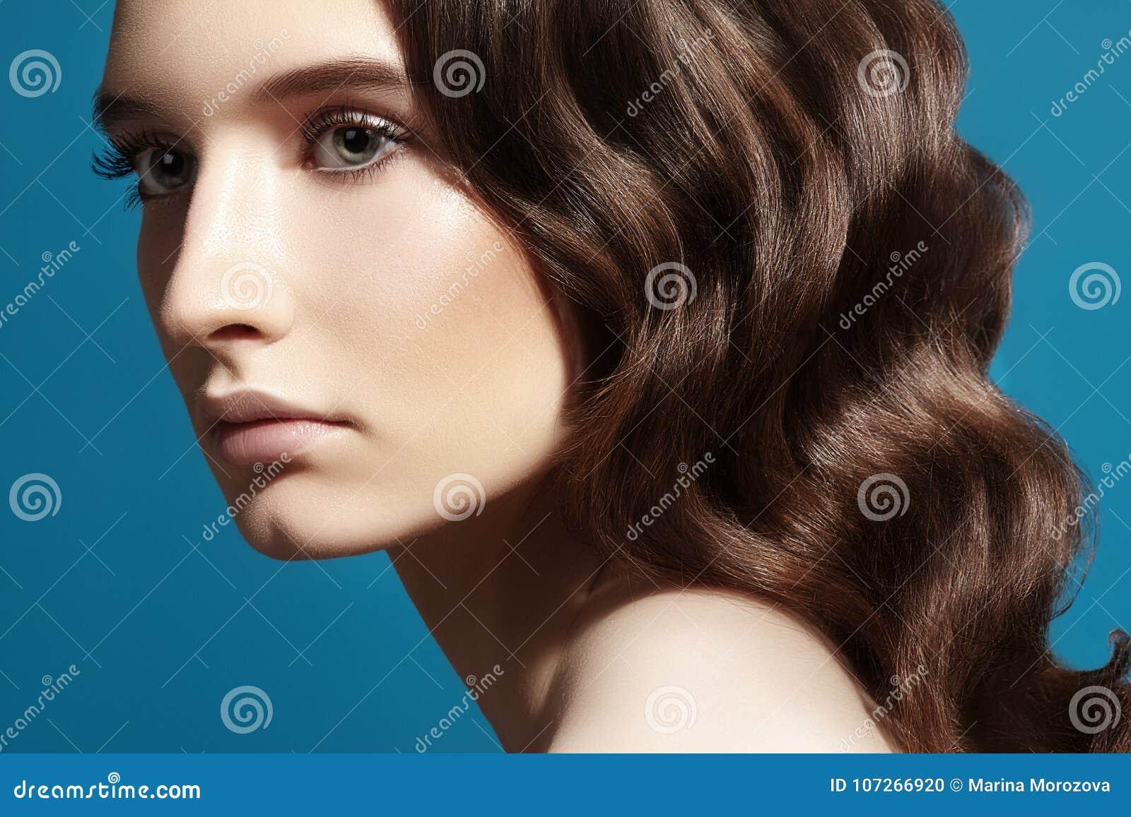 Modelo bonito da mulher do encanto com composição fresca, penteado ondulado romântico Cabelo encaracolado, estilo brilhante liso
