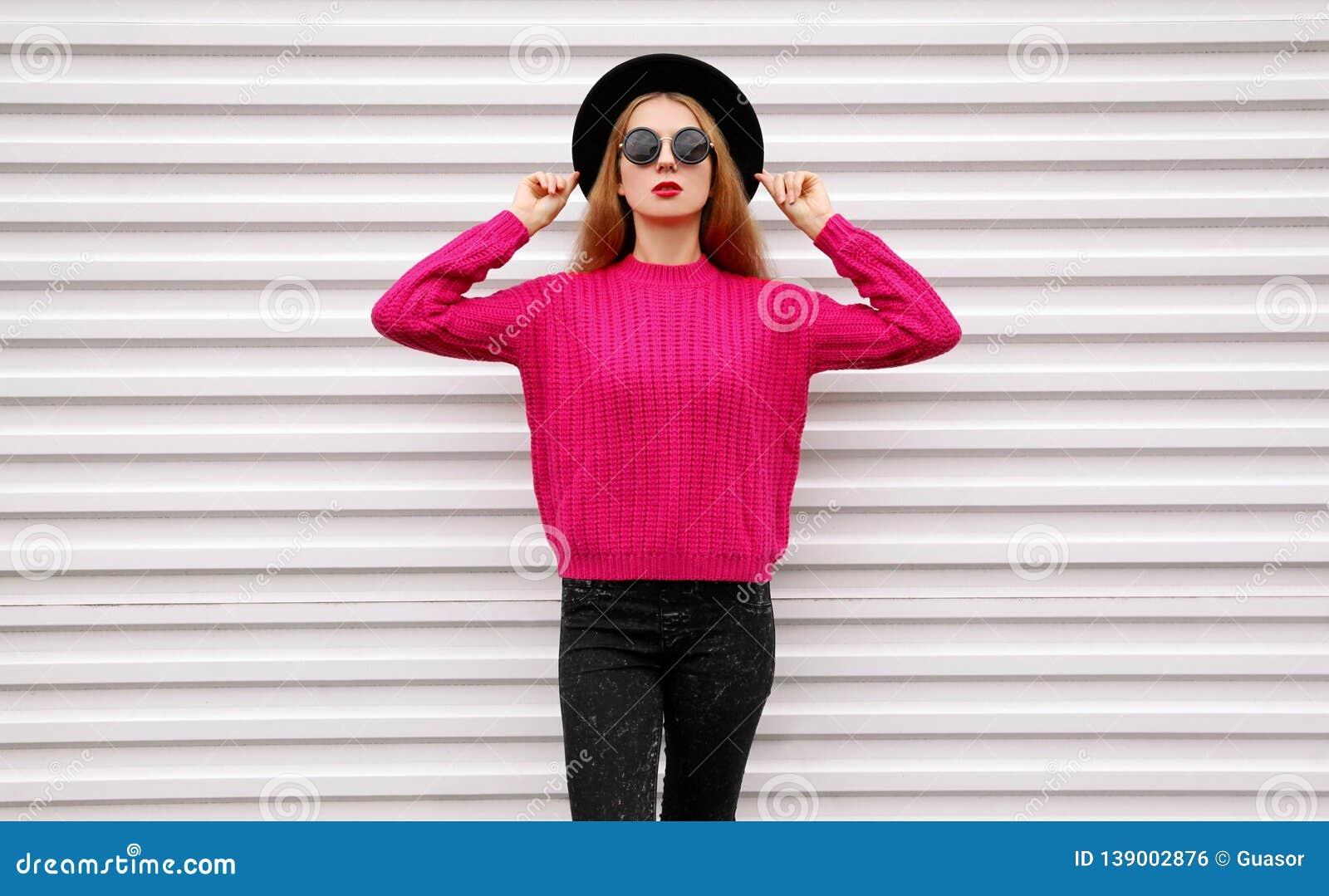 Modelo bonito elegante de la mujer que presenta en el suéter hecho punto rosado colorido, sombrero redondo negro en la pared blan