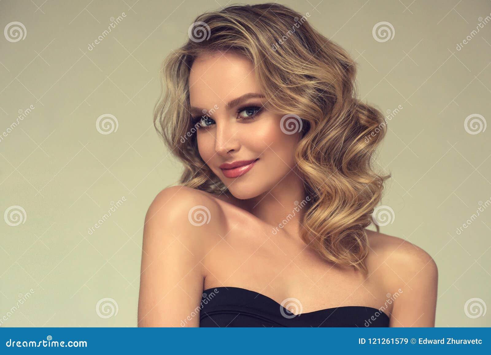 Modelo consideravelmente louro-de cabelo com penteado encaracolado, fraco e composição atrativa